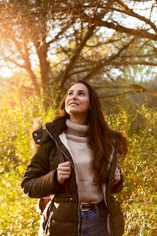 自然を探索しながら太陽の下でポーズ笑顔の女性
