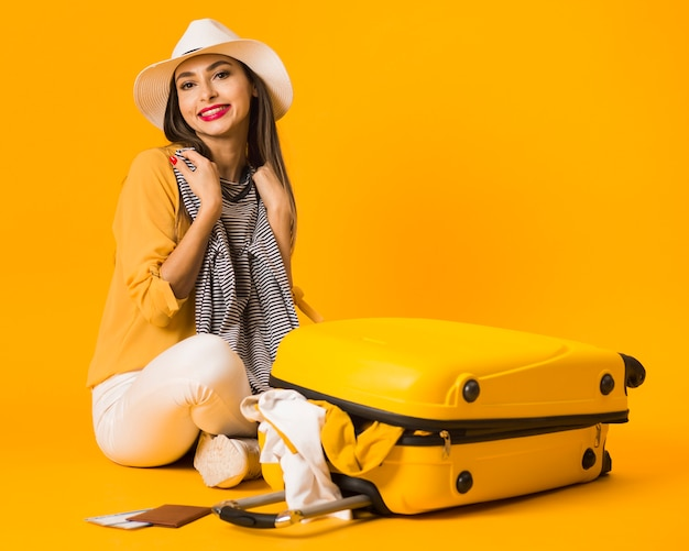Smiley woman posing next to luggage being ready for vacation