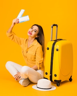 Smiley woman posing next to luggage while holding plane tickets