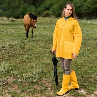 Смайлик женщина позирует рядом с лошадью на открытом воздухе