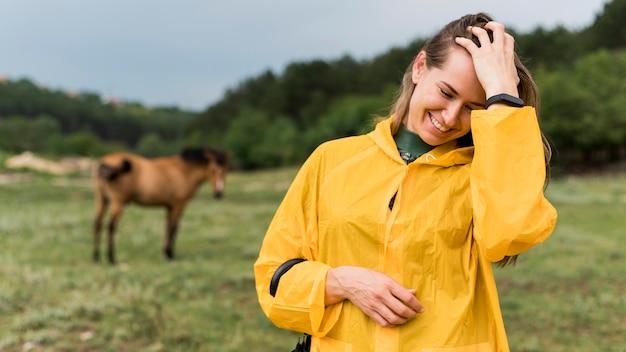 スマイリー女性が馬の横にポーズ