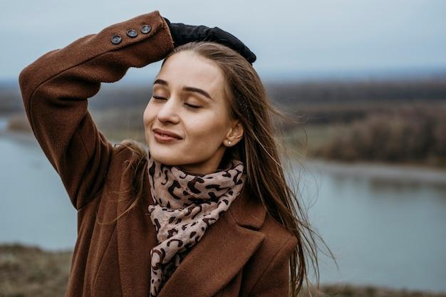 Смайлик женщина позирует на открытом воздухе у озера