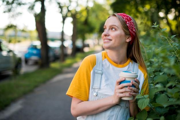 Donna di smiley che propone all'aperto con la tazza