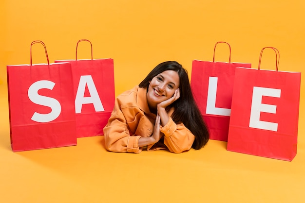 Smiley woman posing in between sale shopping bags
