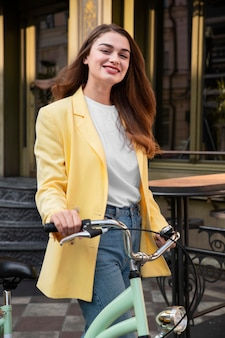 Smiley woman posing in the street while holding her bicycle
