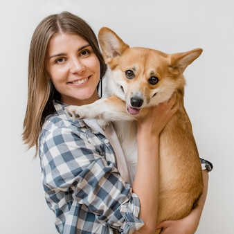 スマイリー女性が彼女の愛らしい犬を押しながらポーズ