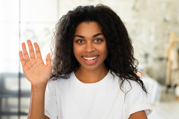 Smiley woman posing while holding her hand up