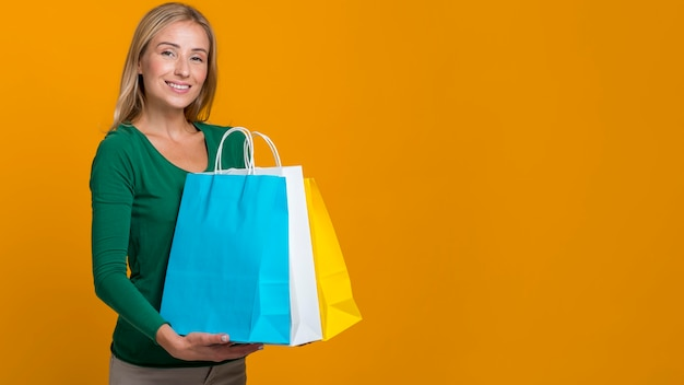 Smiley woman posing while holding lots of shopping bags with copy space