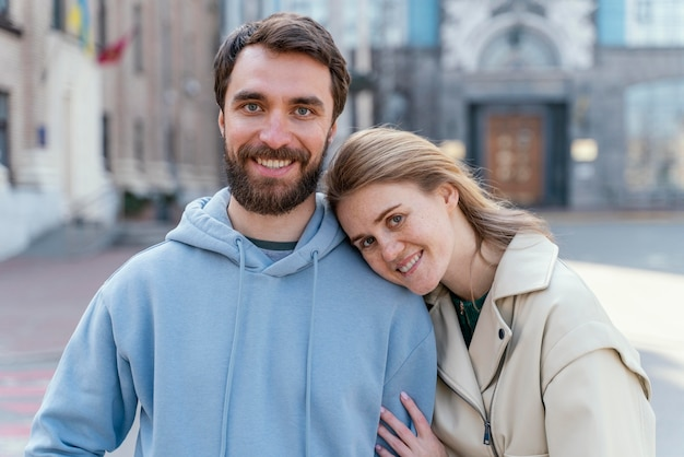 Smiley woman posing while leaning against a man outdoors