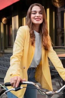 Смайлик женщина позирует во время езды на велосипеде на городской улице