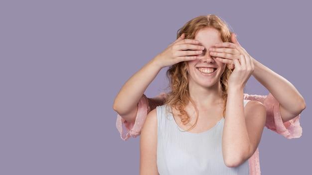 웃는 여자 복사 공간이 그녀의 눈을 덮고 손으로 포즈