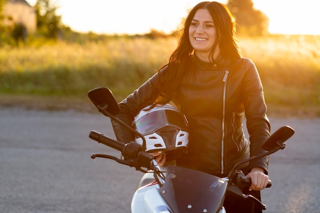 Smiley woman posing with helmet on her motorcycle