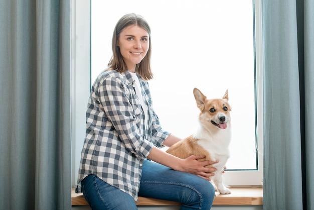 Смайлик женщина позирует со своей собакой перед окном