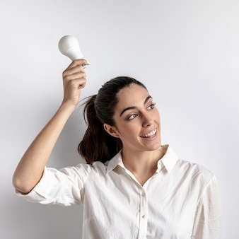Smiley woman posing with light bulb
