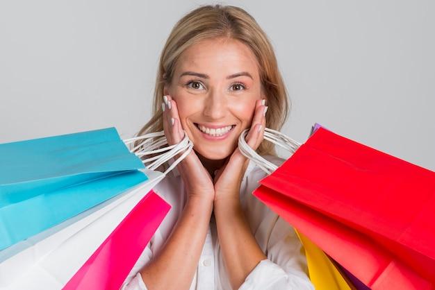 Donna di smiley in posa con molte borse della spesa colorate