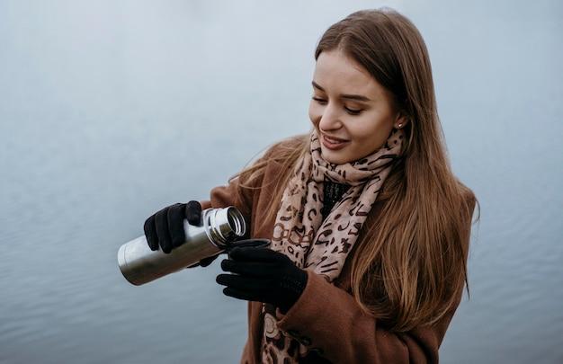 Смайлик женщина наливает горячий напиток на берегу озера