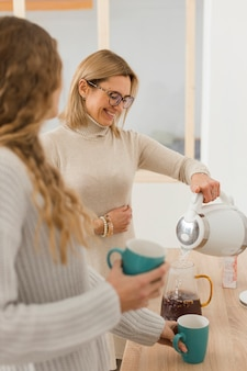 Smiley woman pouring water in a carafe