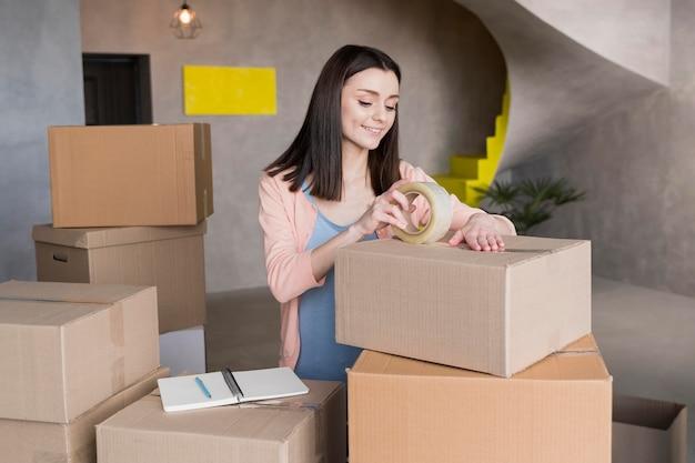 発送用の箱を準備するスマイリー女性