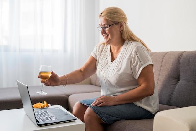 Donna sorridente in quarantena con un drink con il computer portatile