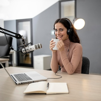 Smiley woman in a radio studio with microphone and coffee