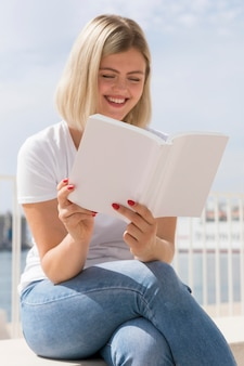 Smiley woman reading a book outdoors