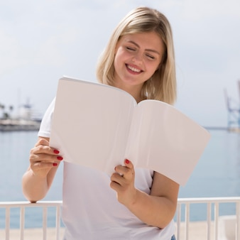 Smiley woman reading book outside