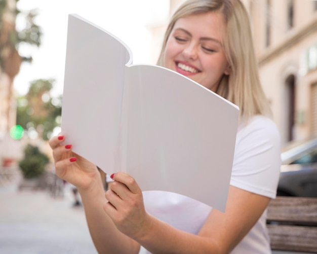 Smiley woman reading book while sitting on bench outside