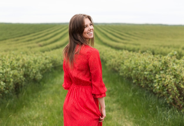 Smiley woman in red in field