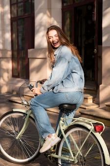 Улыбающаяся женщина, едущая на велосипеде на улице в городе