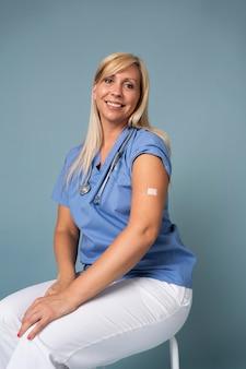 백신 접종 후 스티커로 팔을 보여주는 웃는 여자