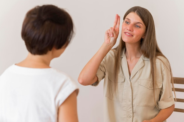 Smiley woman showing sign language to another person