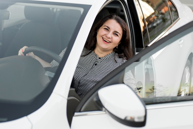 Smiley woman sitting in the driver seat