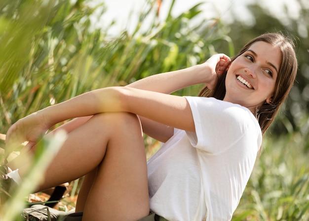 Donna sorridente che si siede sull'erba