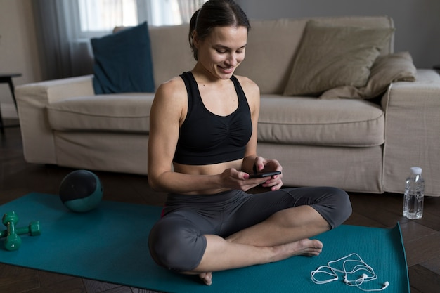 Смайлик женщина сидит на коврик для йоги и смотрит на телефон