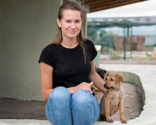 Donna sorridente che si siede accanto al cane di salvataggio al riparo