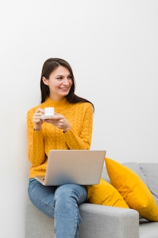 Smiley woman sitting on sofa next to laptop and holding cup of coffee