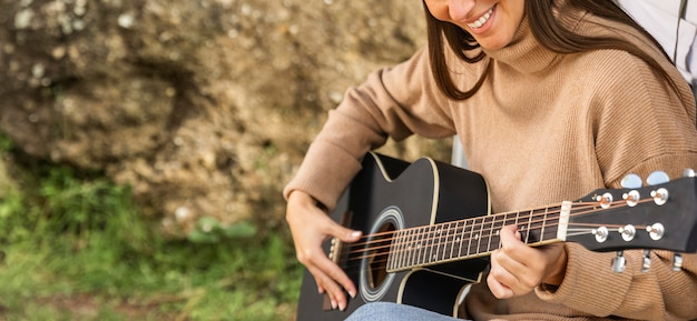 Smiley woman sitting in the trunk of the car while on a road trip and playing guitar