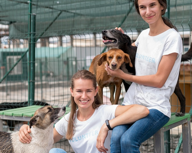避難所でかわいい救助犬と一緒に時間を過ごすスマイリー女性