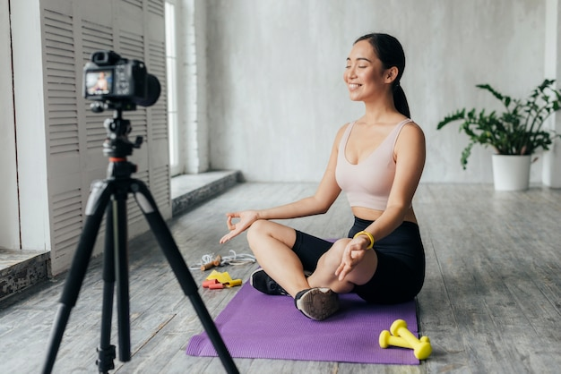Smiley woman in sportswear vlogging while meditating