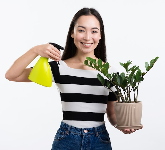 Smiley woman spraying flower leaves