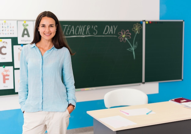Smiley woman standing in the classroom