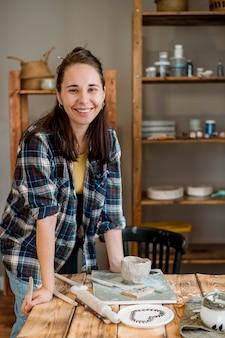 Donna sorridente in piedi nel suo laboratorio di ceramica
