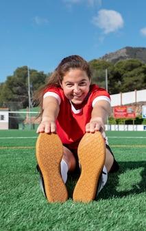 Donna di smiley che allunga la gamba sul campo
