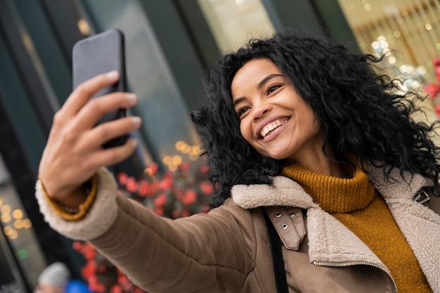 밖에 서 그녀의 스마트 폰으로 selfie를 복용 웃는 여자
