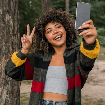 Smiley woman taking selfie while camping outdoors