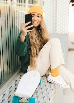 Smiley woman taking selfie with skateboard
