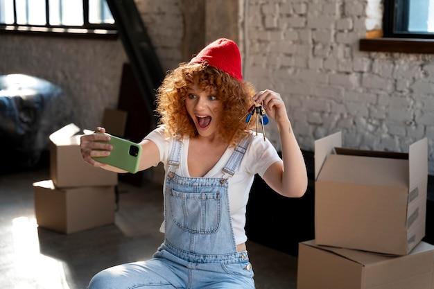 鍵を持って新しい家でスマートフォンで自分撮りをしているスマイリー女性