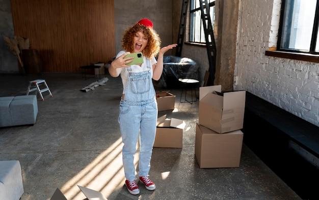 彼女の新しい家でスマートフォンで自分撮りをしているスマイリー女性