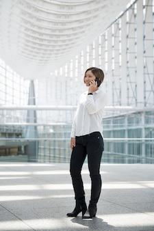 Smiley woman talking on phone full shot