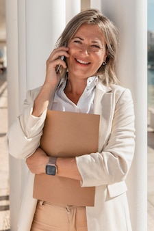 Donna di smiley che parla sul colpo medio del telefono